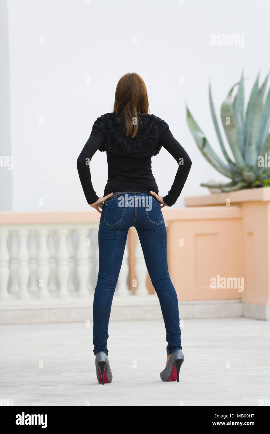 Young adult-girl in denim pants from rear standing in high heels has having have leggy Stock Photo