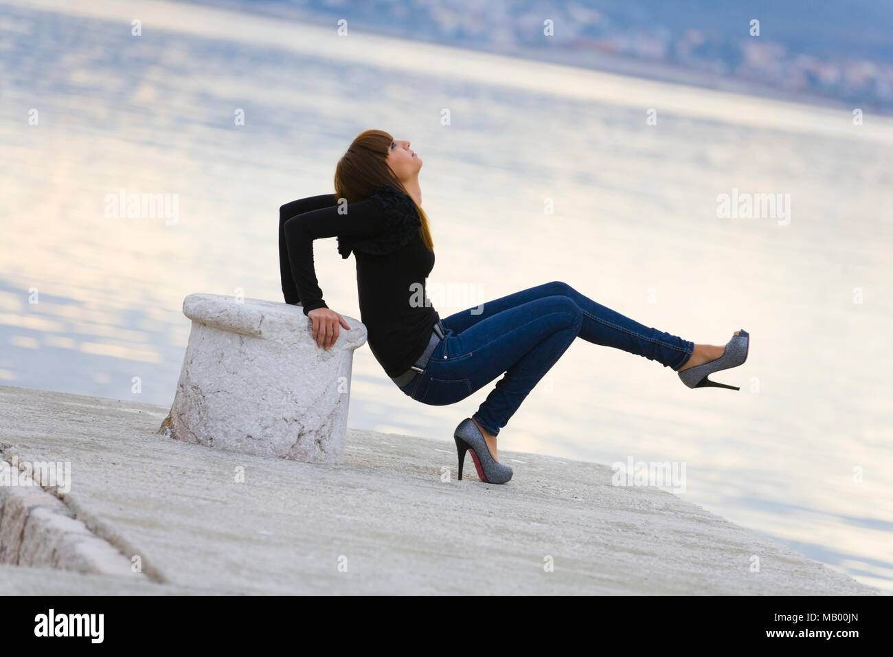 High heels and denims balancing on one leg sideways view wobbly balance spike spiked Stock Photo