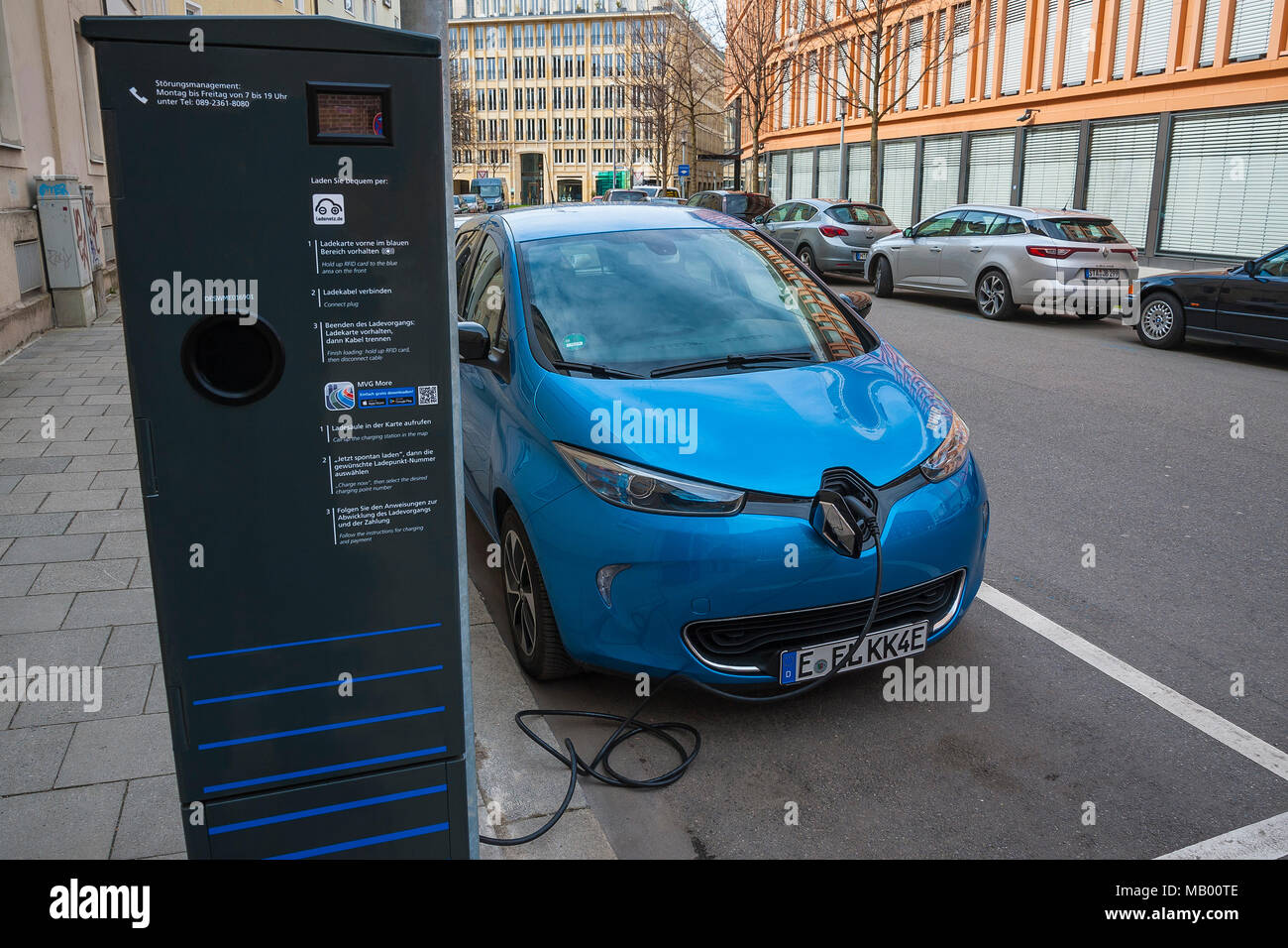 Electric car is charged at green electricity charging station with charging cable, Munich, Bavaria, Germany - Stock Image
