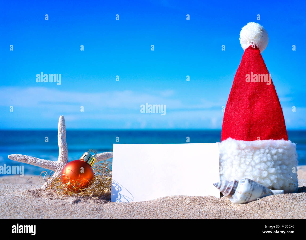Christmas greeting card and christmas decoration on the beach. Beach scene with starfish, shells and sand. Christmas tree ball and blank white card. - Stock Image