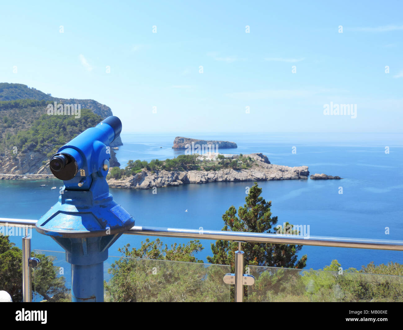 Lookout point with binoculars or telescope. Ibiza viewpoint onto a cliff coast. - Stock Image