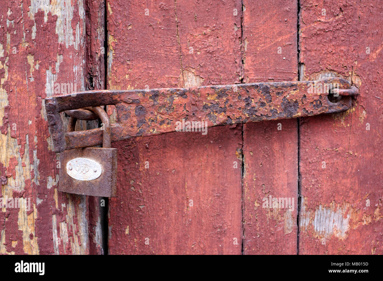 An old wooden door with a rusty lock - Stock Image