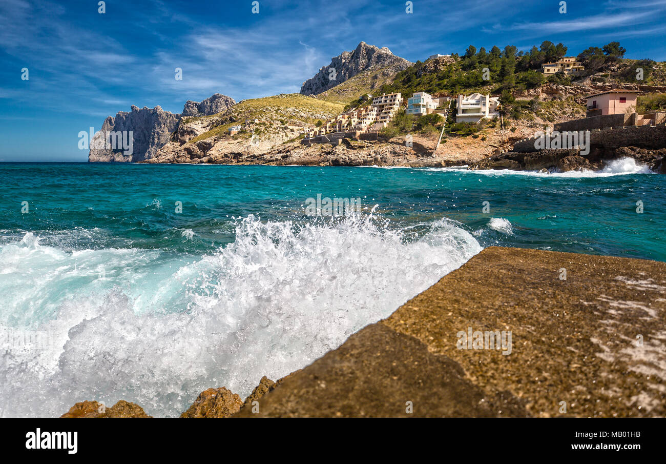 Splashing Water on the Pier of the Small Town Cala Sant Vincenc - Stock Image