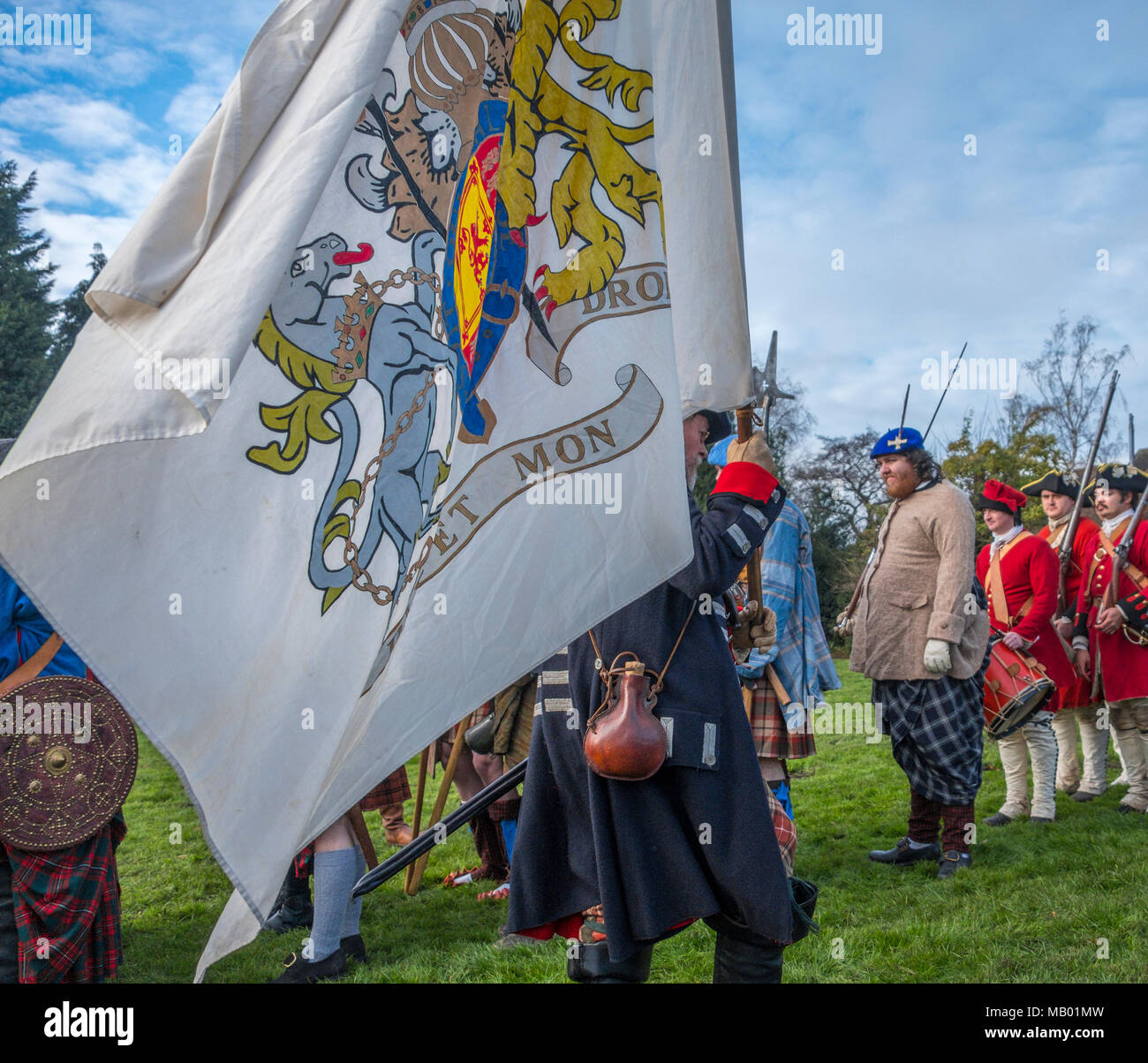 Supporters of Charles Edward Stuart better known as Bonnie Prince Charlie around their colours at a reenactment of the Jacobite rising of 1745. Stock Photo