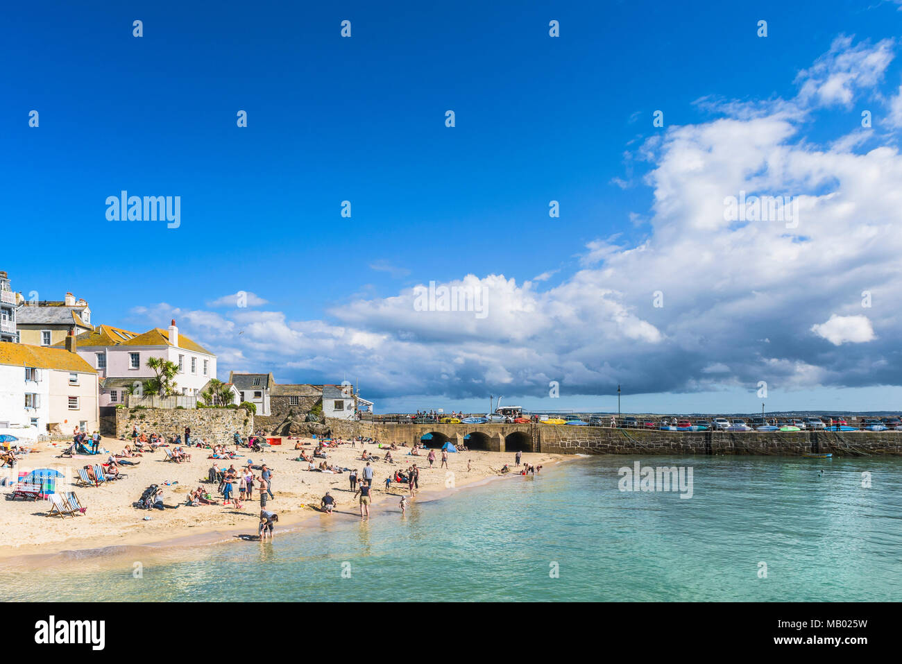 Holidaymakers relaxing on St Ives Harbour Beach in Cornwall. - Stock Image