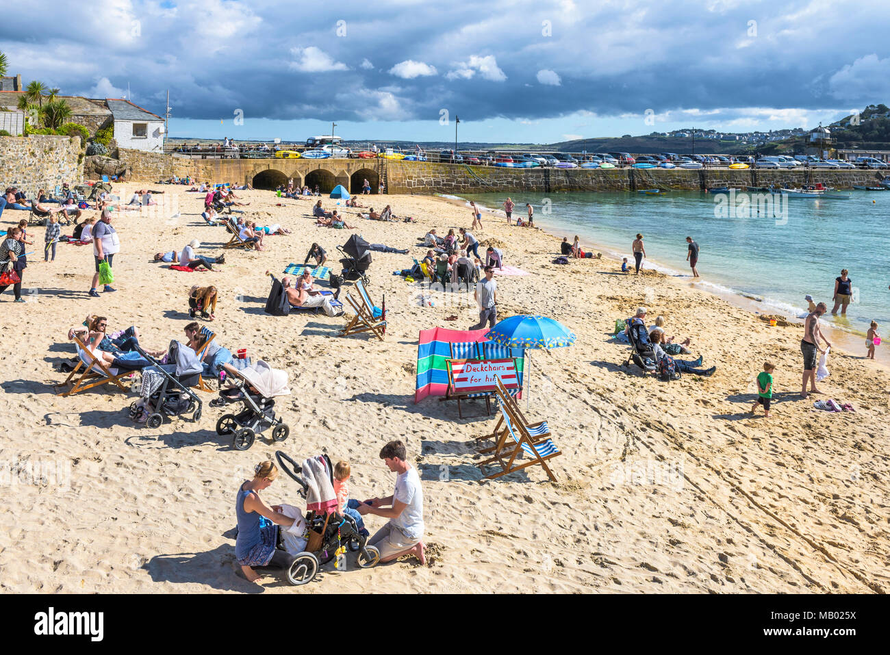Holidaymakers relaxing on St Ives Harbour Beach in St Ives in Cornwall. - Stock Image