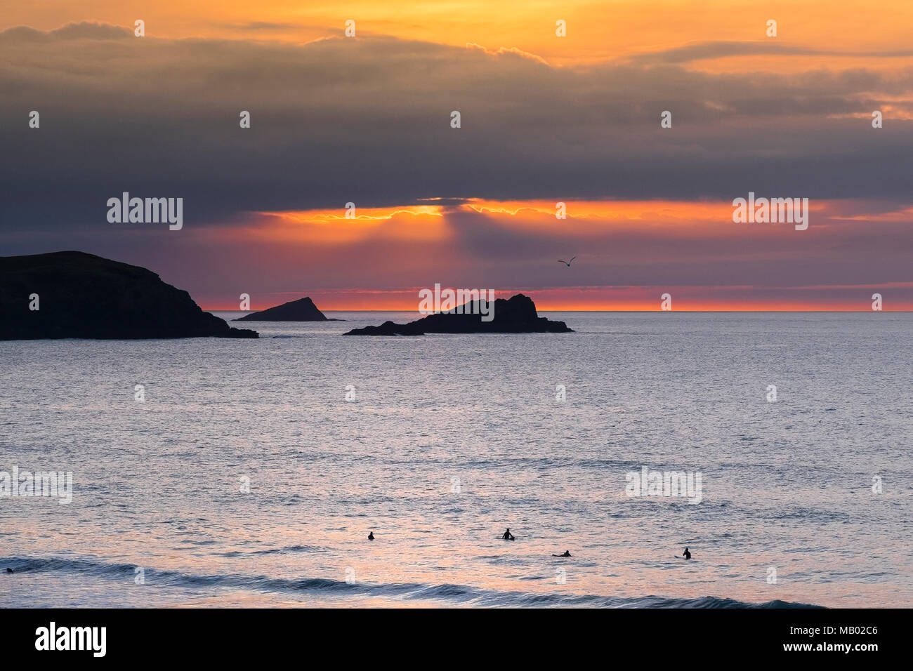 The Goose and The Chick small islands off East Pentire Headland are seeen in silhouette as the sun sets over Fistral in Cornwall. Stock Photo
