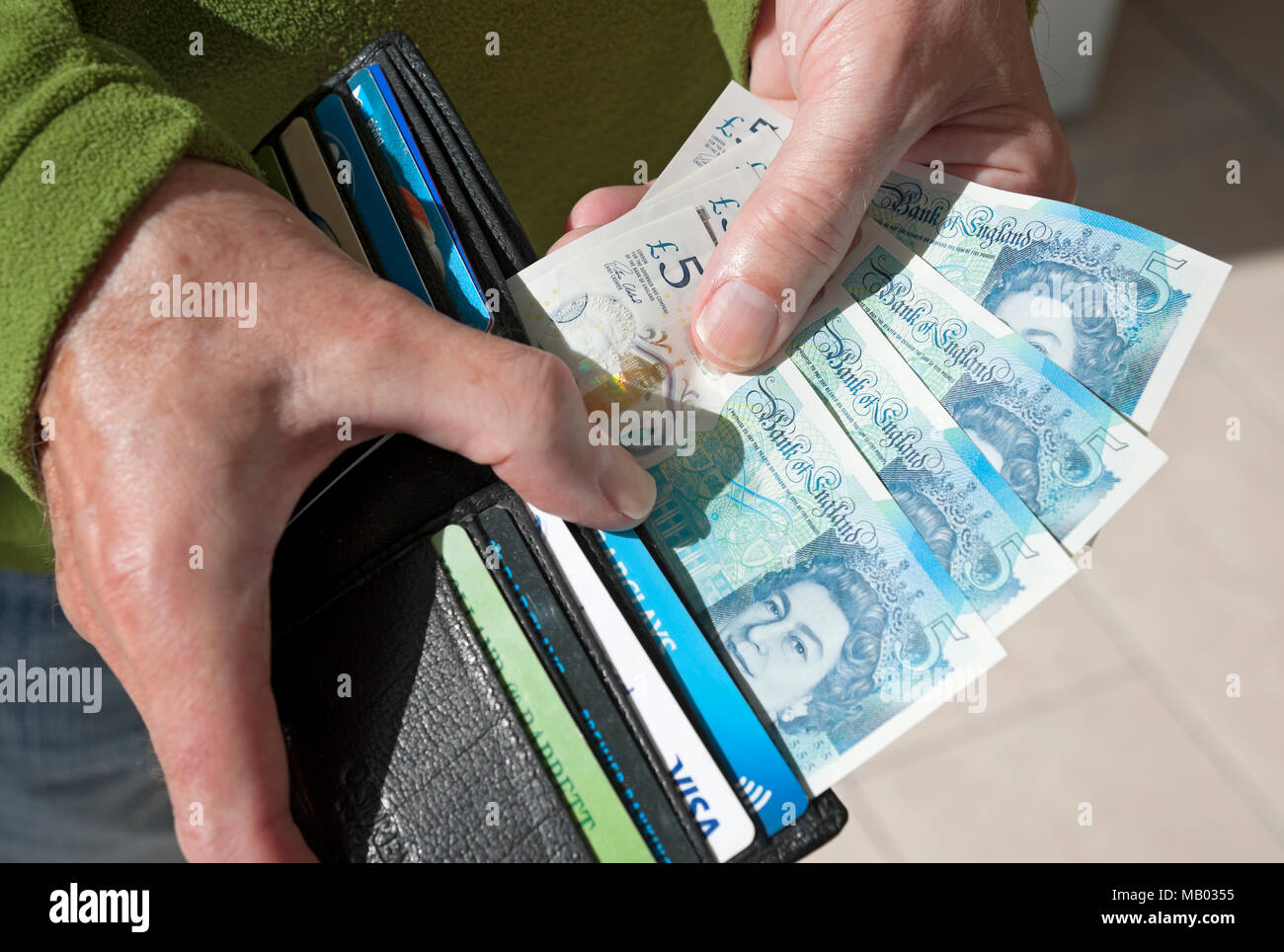 Man holding new polymer five pound notes. - Stock Image