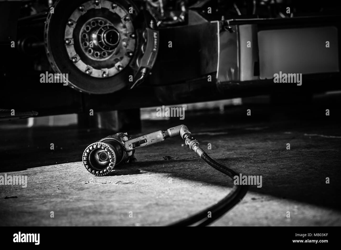 Black & White abstract image of LMP1 Le Mans Prototype wheel gun on Pit Garage floor during Master Historic Racing Test Day at Brands Hatch Circuit - Stock Image