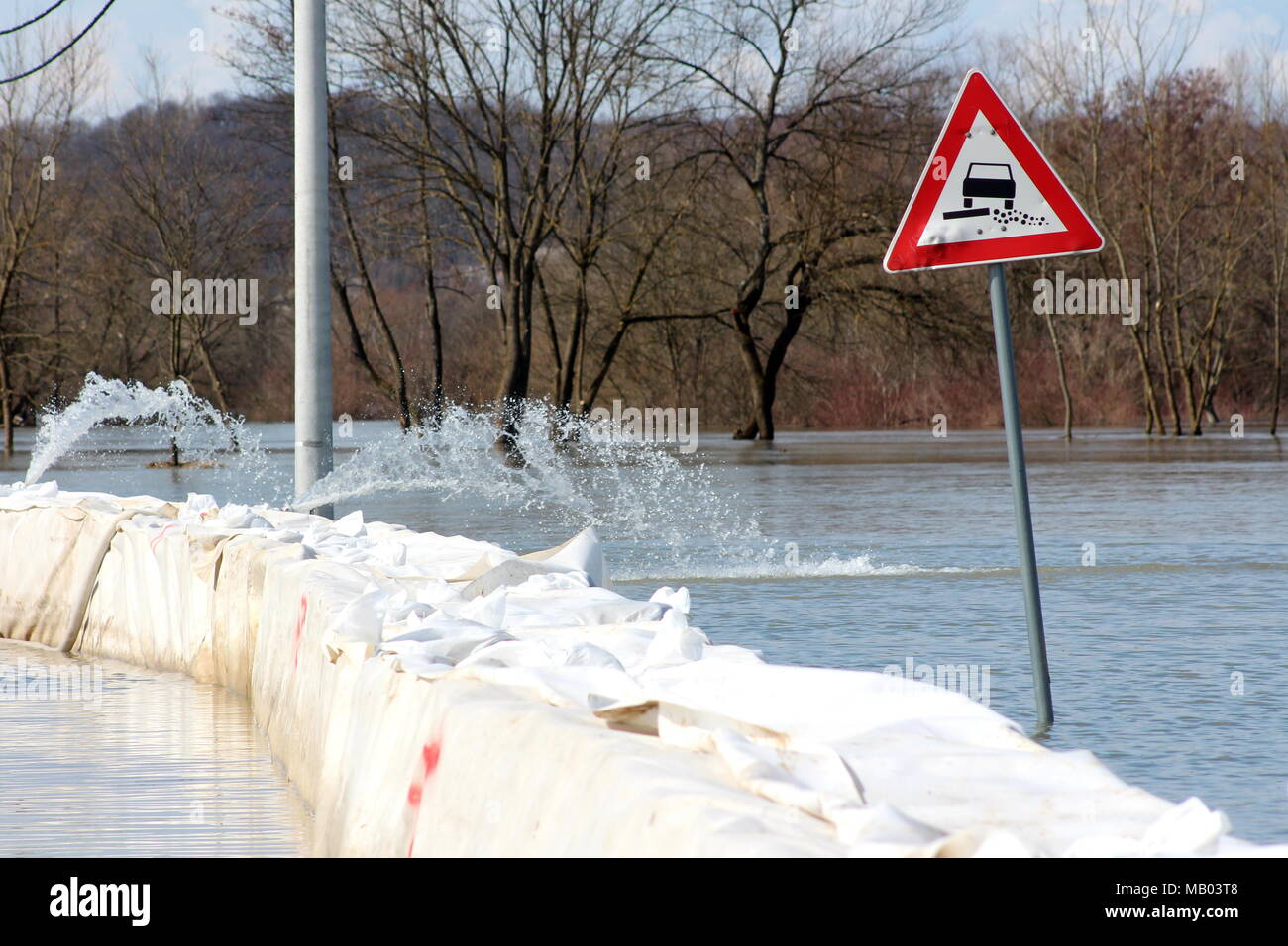 Flooded soft verge road sign next to box barriers flood protection with pumps pumping water, trees, branches, concrete electrical pole and blue sky in - Stock Image