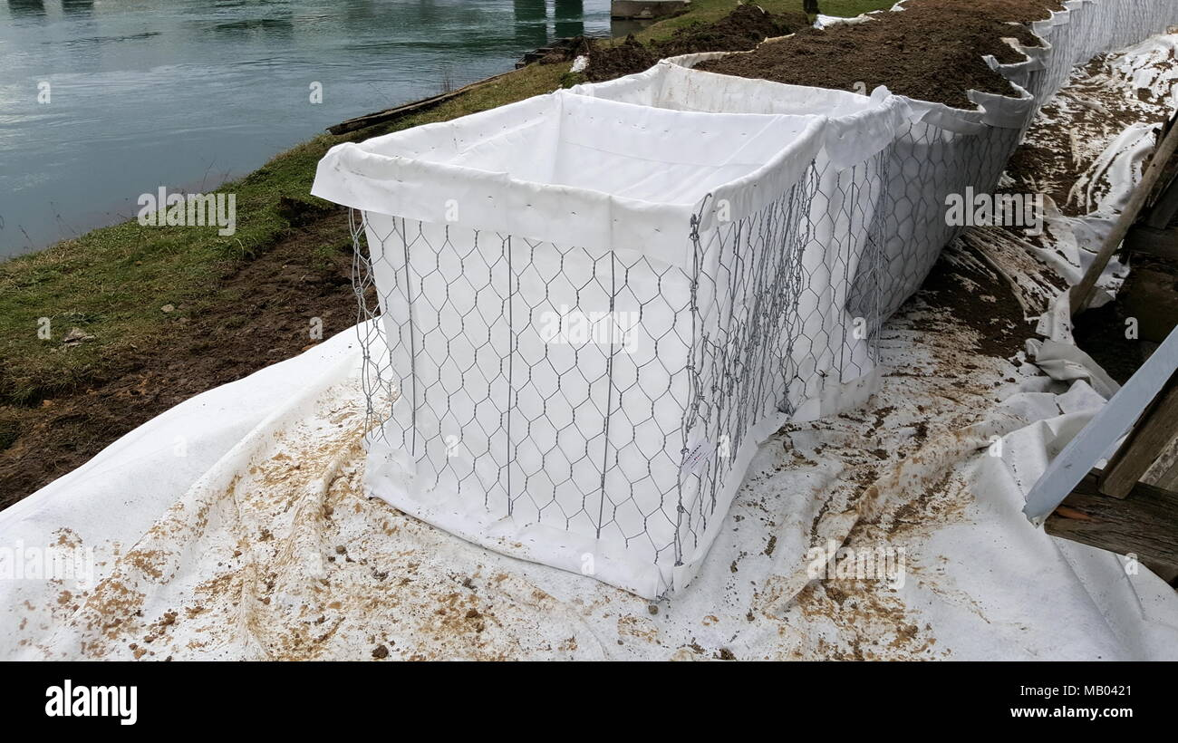 Setting up new sandbox barriers flood protection next to mighty river in preparation for oncoming flood - Stock Image