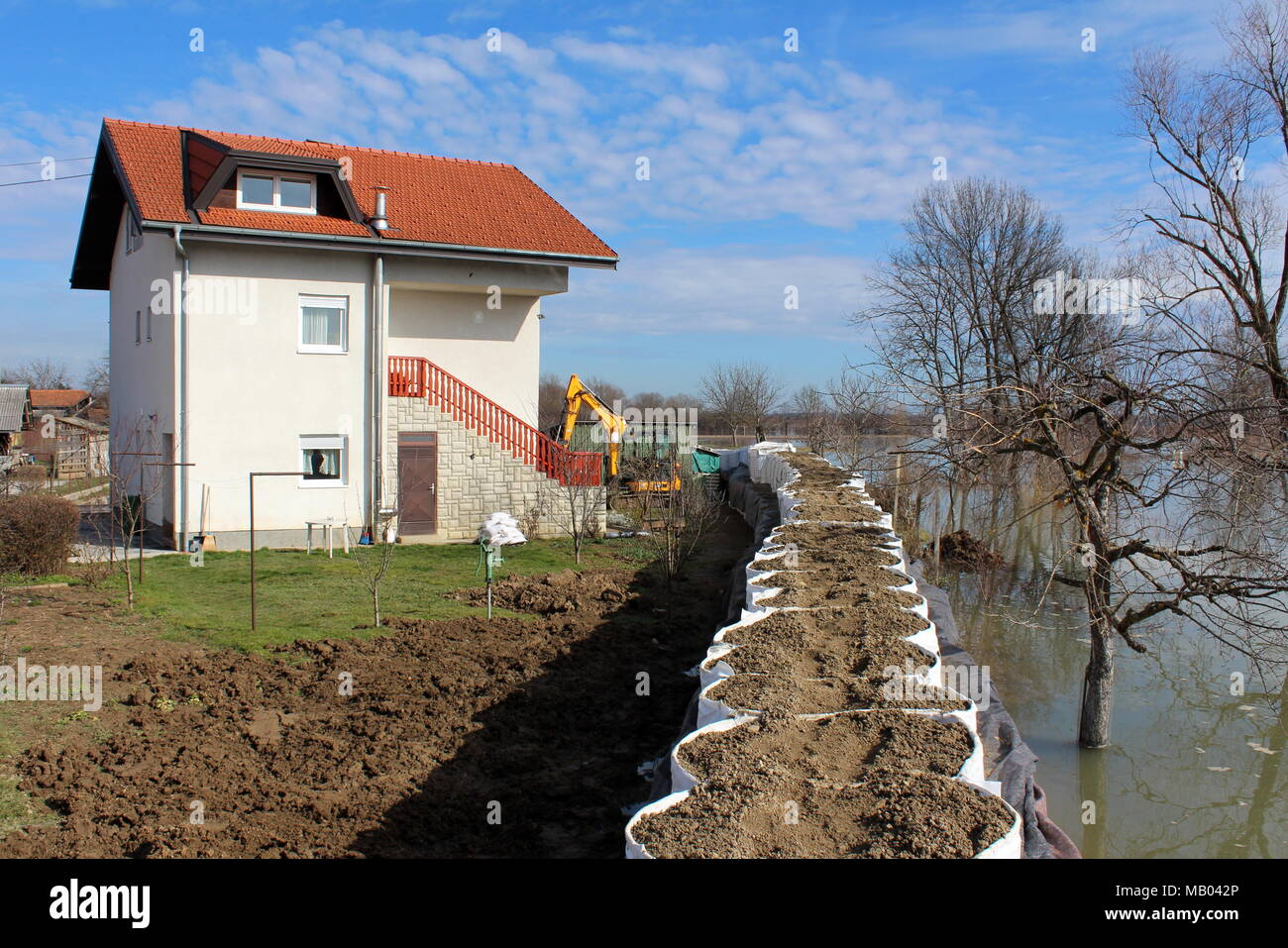Suburban house protected with flood protection from rising river Stock Photo