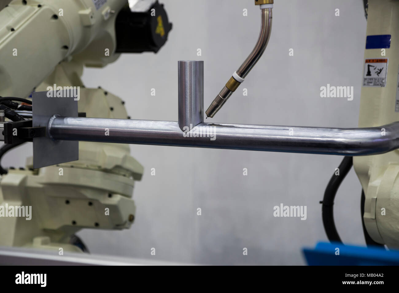 Robot arm welding pipe ; focus at torch - Stock Image