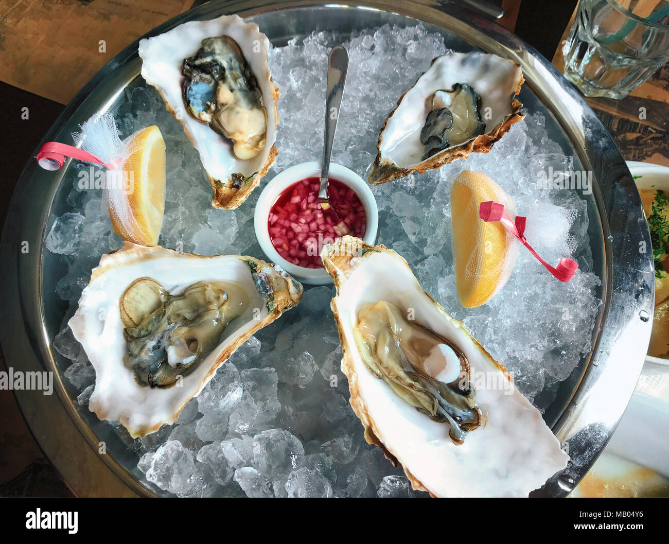 A large platter with delikatesnye oysters on ice with lime served with champagne and herbs. Serving. The horizontal frame. Stock Photo
