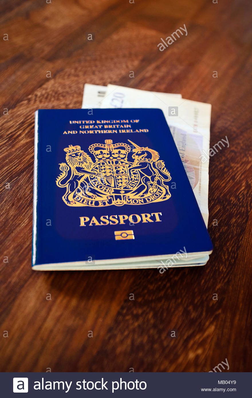 Brexit Ready - A blue coloured UK passport with UK pound sterling currency bank notes. - Stock Image