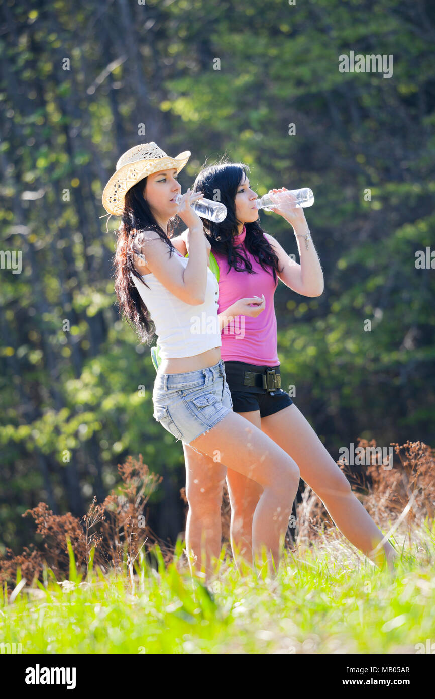 Two girls are drinking water bokeh apparently almost evidently friends friendship girlfriends hands hand - Stock Image