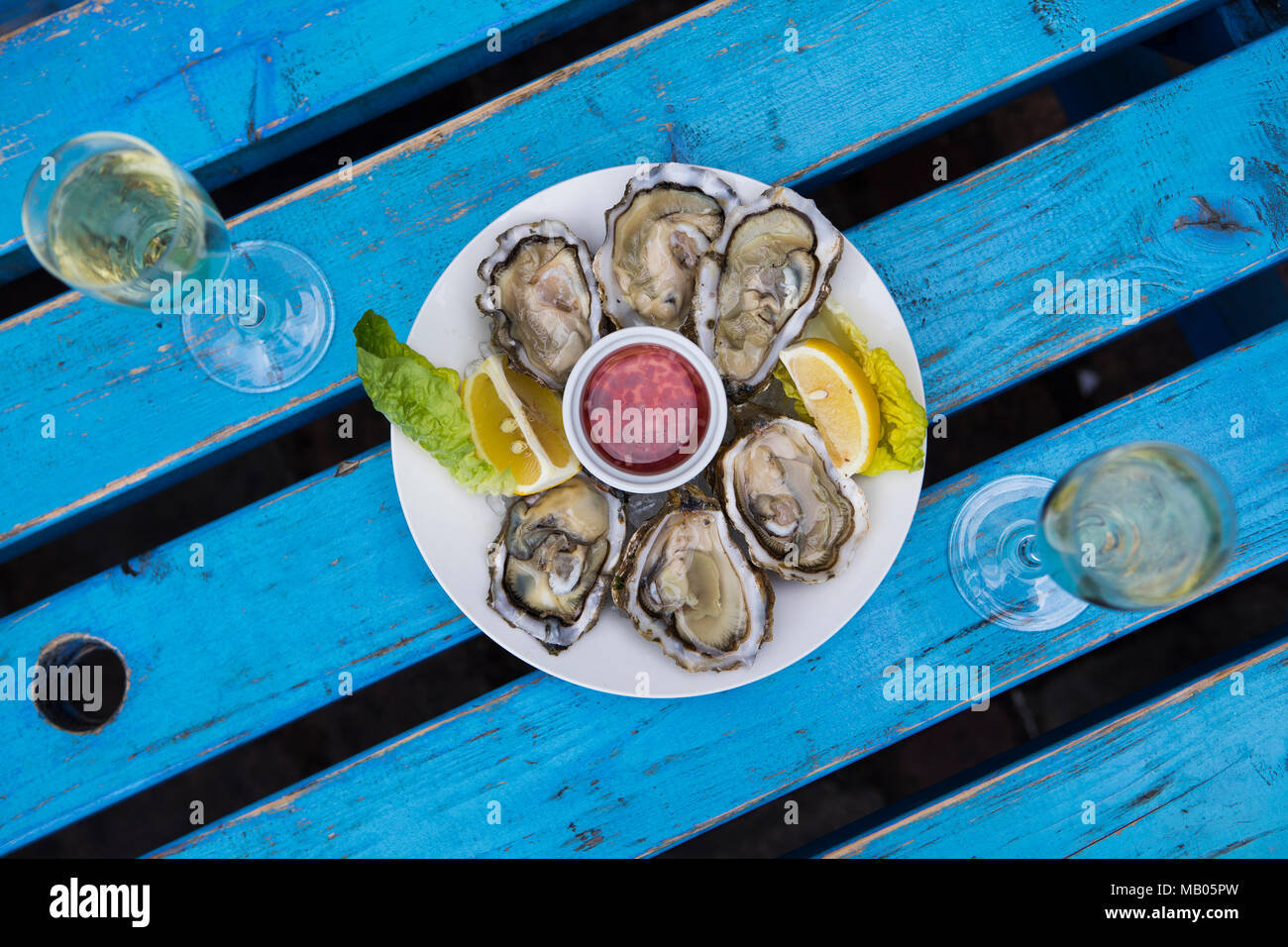 Oysters and champagne with lemon wedge and mignette dressing on white plate on blue distressed vintage table. - Stock Image
