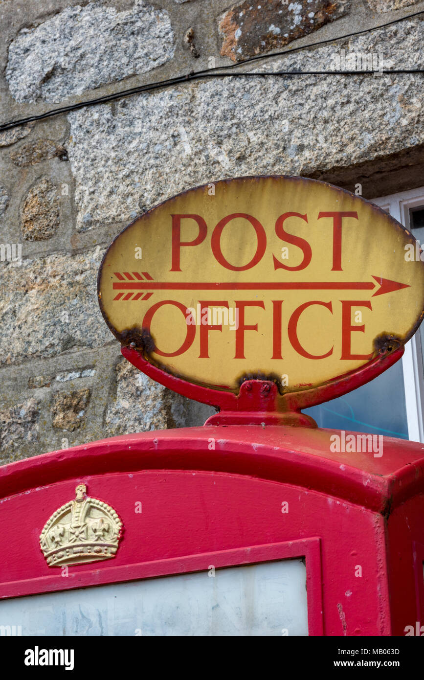 an old vintage post office or postal services signpost on the top of a traditional red gpo post office phone box. English typically British telephone. - Stock Image