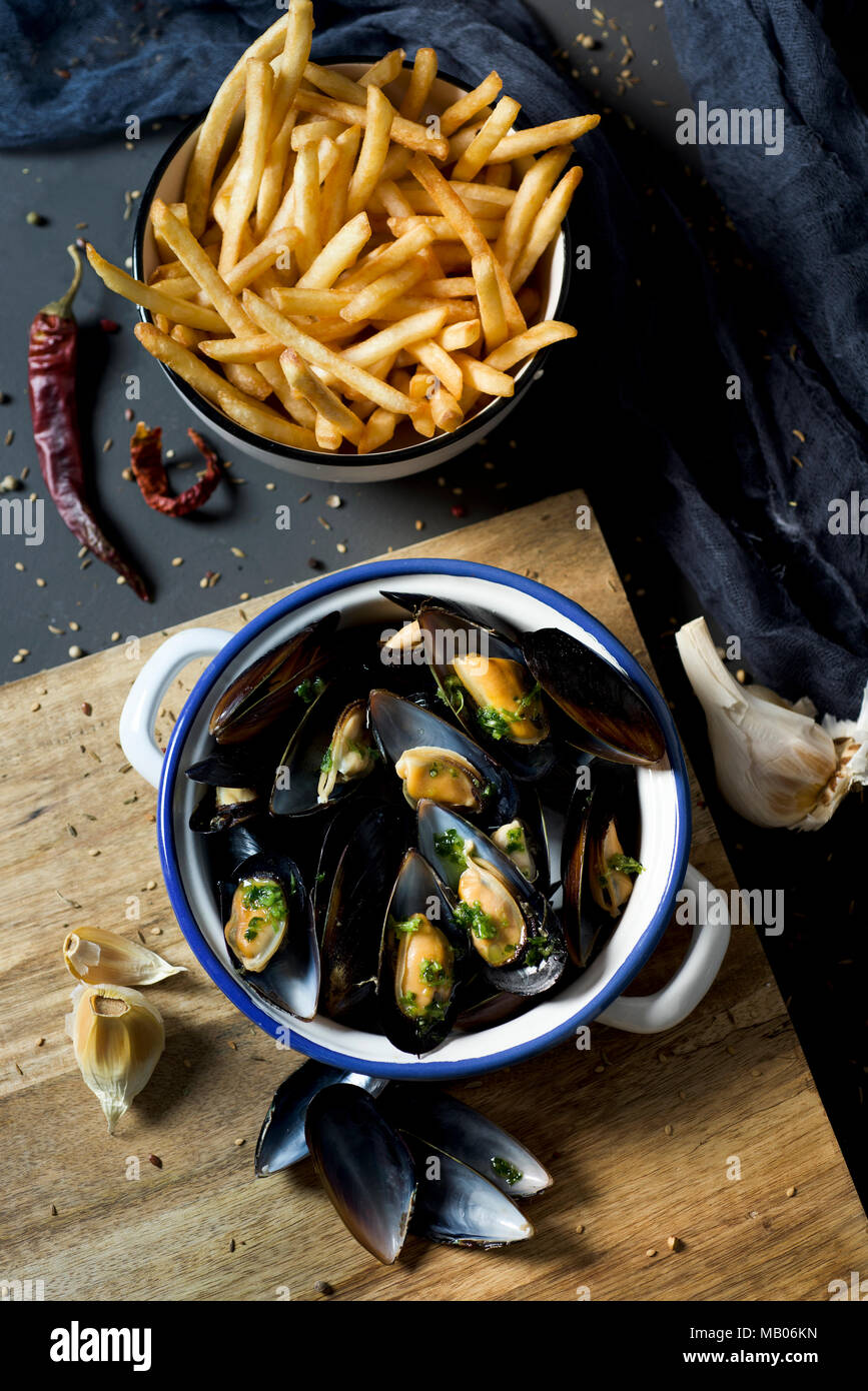 moules-frites, mussels and fries typical of Belgium, on a rustic wooden table - Stock Image