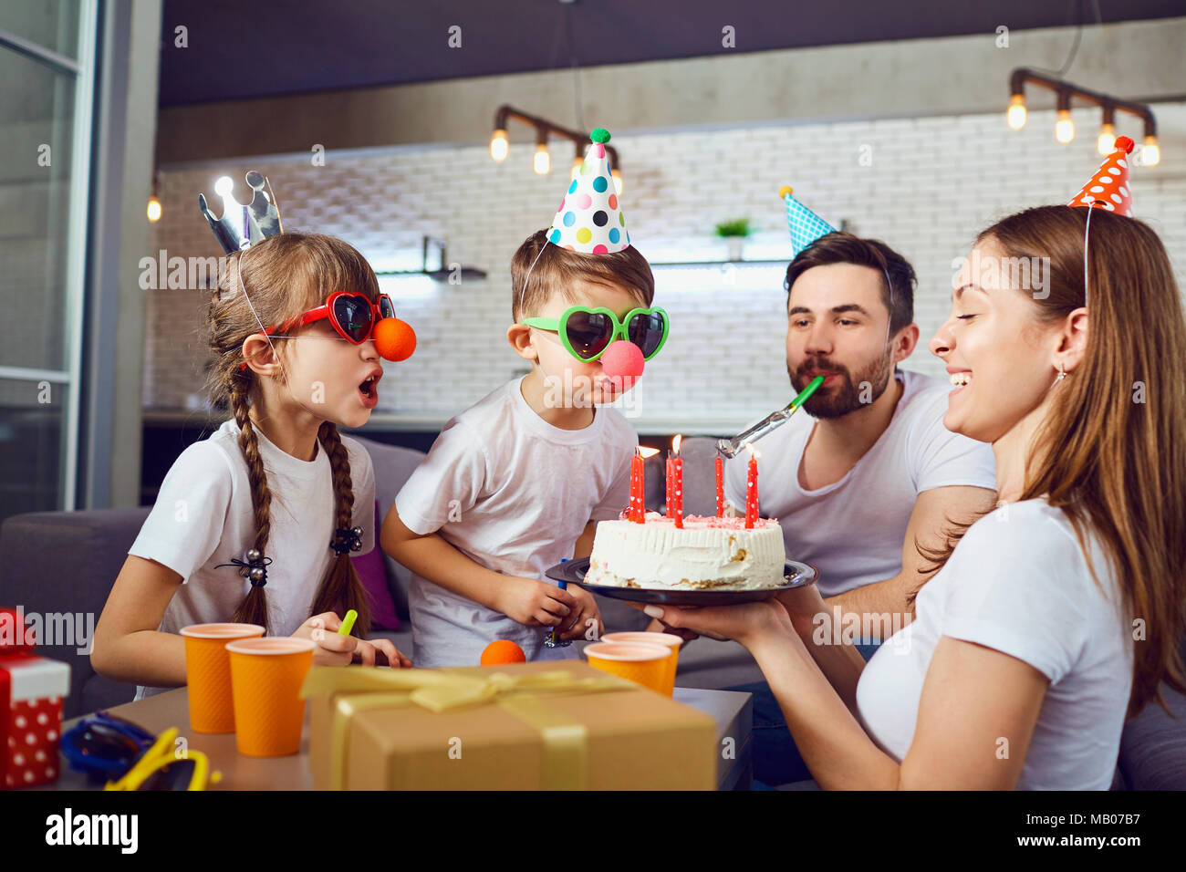 A happy family with a  cake celebrates a birthday party. - Stock Image