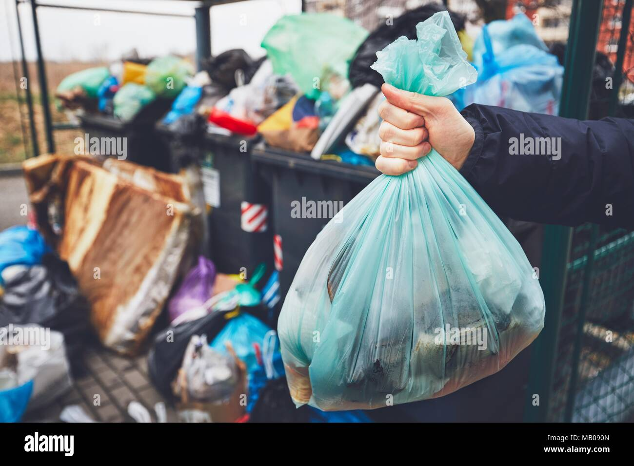 Hand with garbage against full trash cans with rubbish bags overflowing onto the pavement. - Stock Image