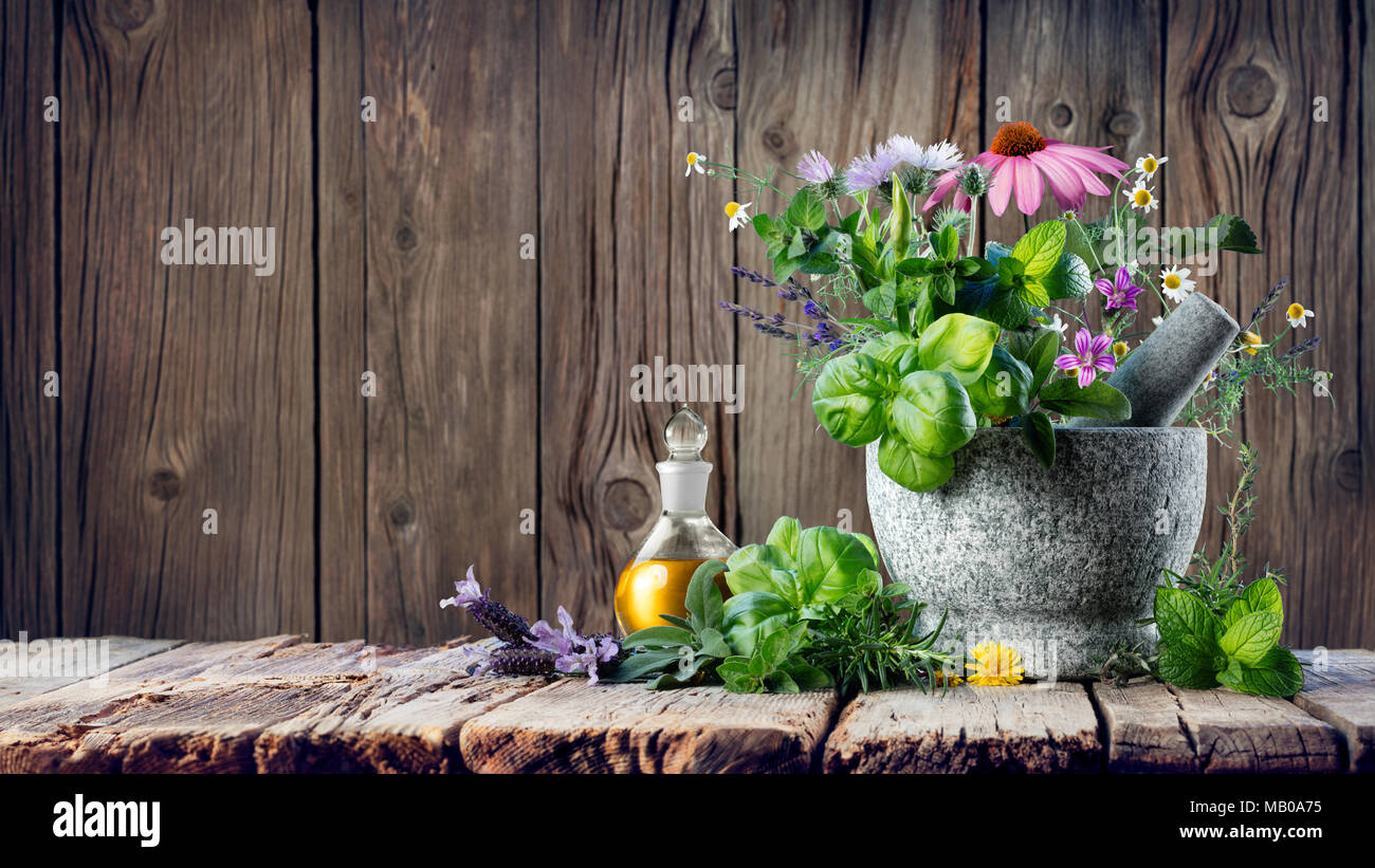 Healing Herbs And Essential Oil In Bottle With Mortar - Homeopathy and Alternative Medicine Stock Photo