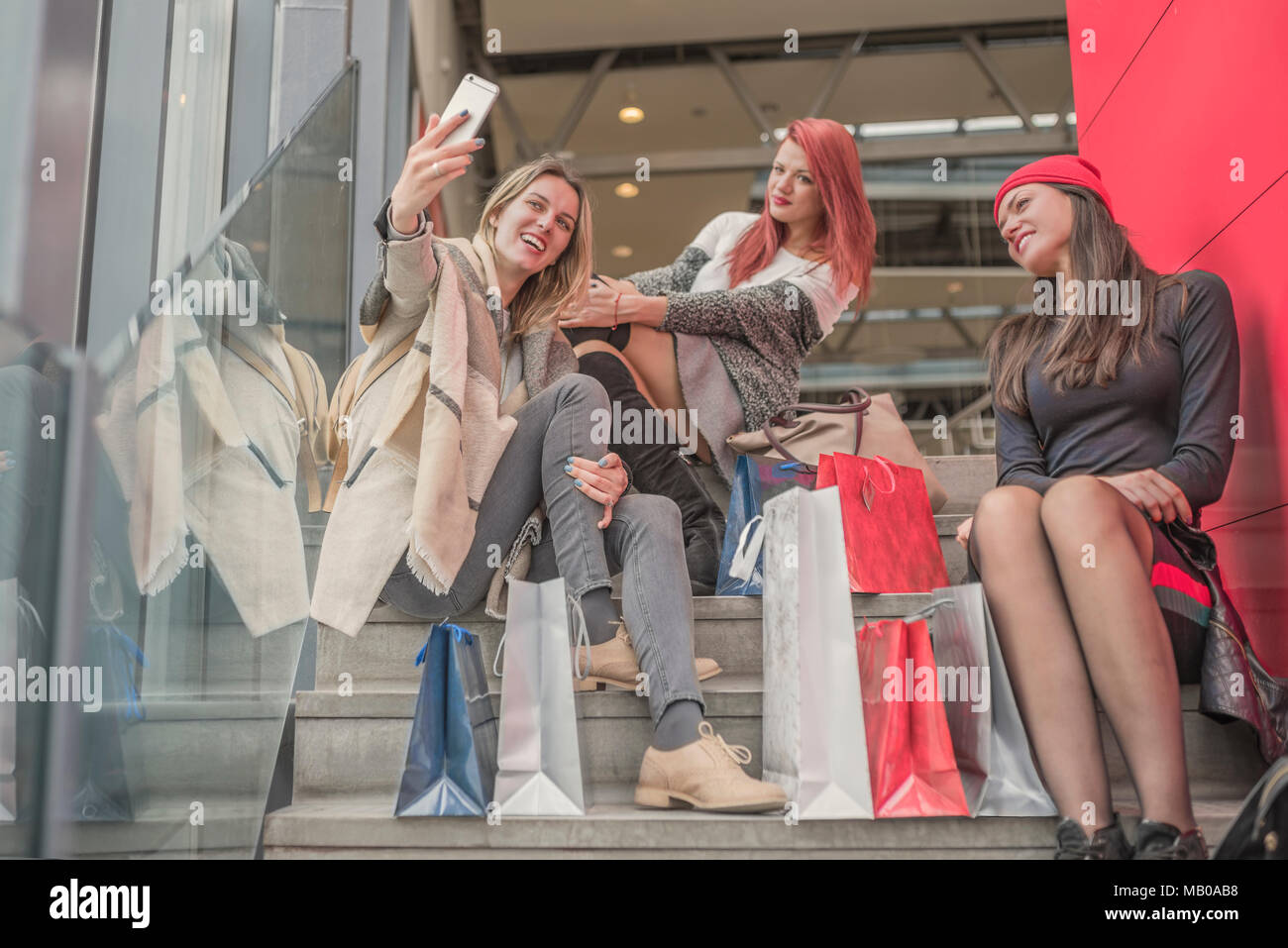 Three young and pretty girls are holding the shopping bags and going forward to the mall. Happy shopping with smiles. Good mood while shopping. - Stock Image