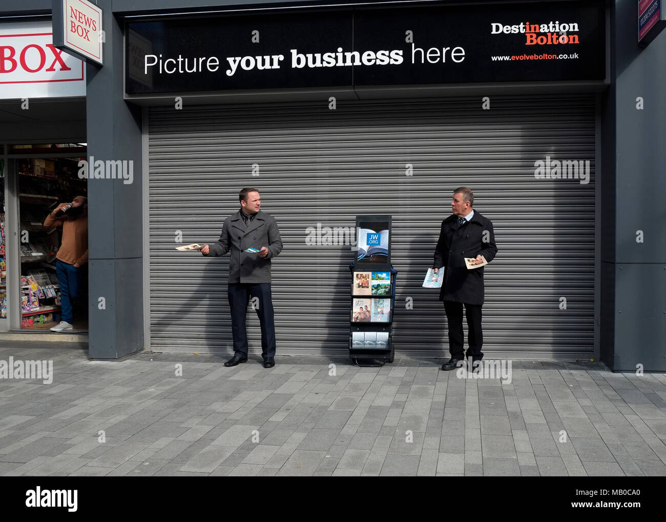 Jehovahs Witnesses handing out religious literature while a Muslim stands in his shop doorway in Bolton Town Centre, England UK.   photo Don Tonge - Stock Image