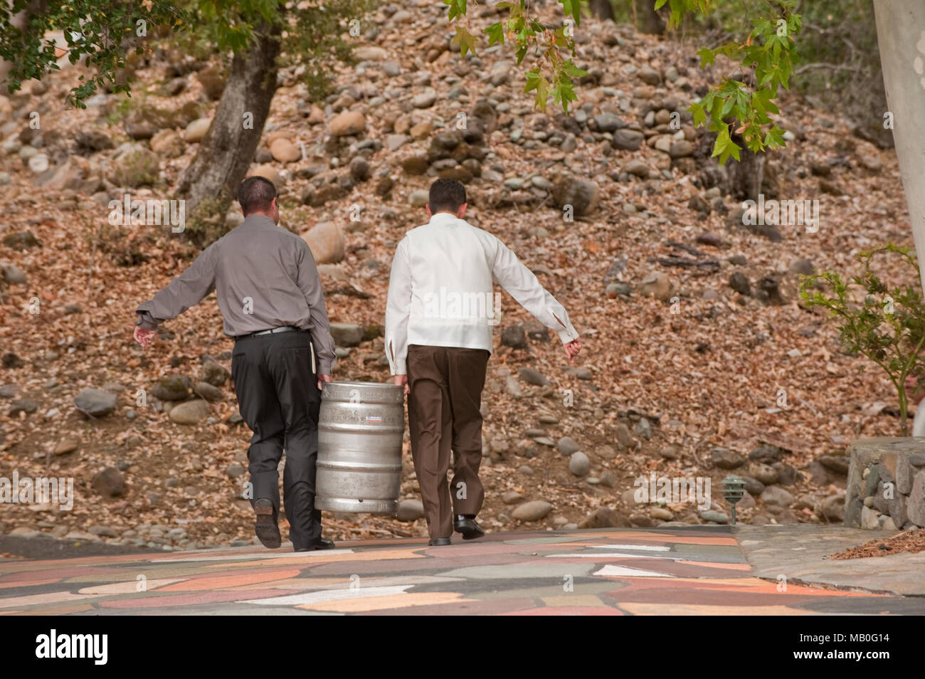 A groomsman and a man carrying a keg of beer for a wedding reception Stock Photo