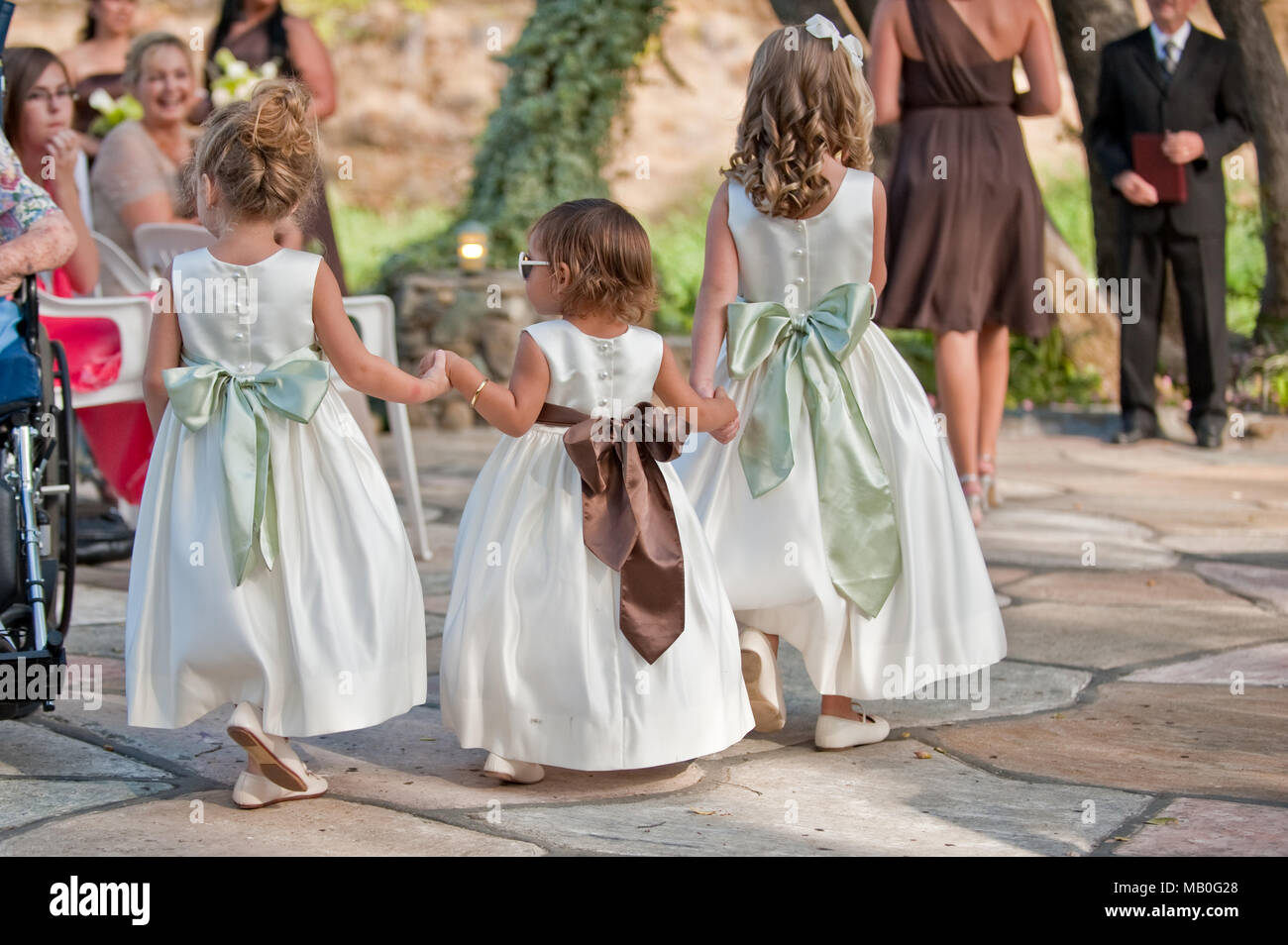 Three little cute girls holding hands and walking the aisle at an outdoor wedding at California - Stock Image