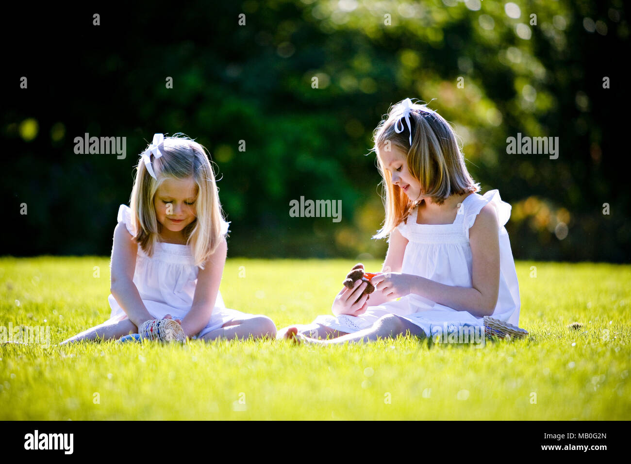 Two young pretty Caucansian girls in white skirts sitting on grass playing at a park with back lighting and blurry green background - Stock Image