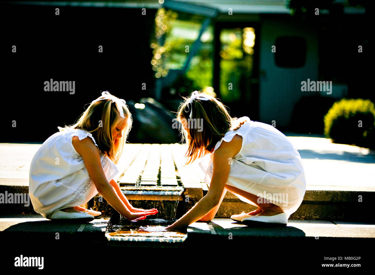 Two pretty young girls in white skirts and white shoes playing with fountain water at a park with sun light shining from behind - Stock Image