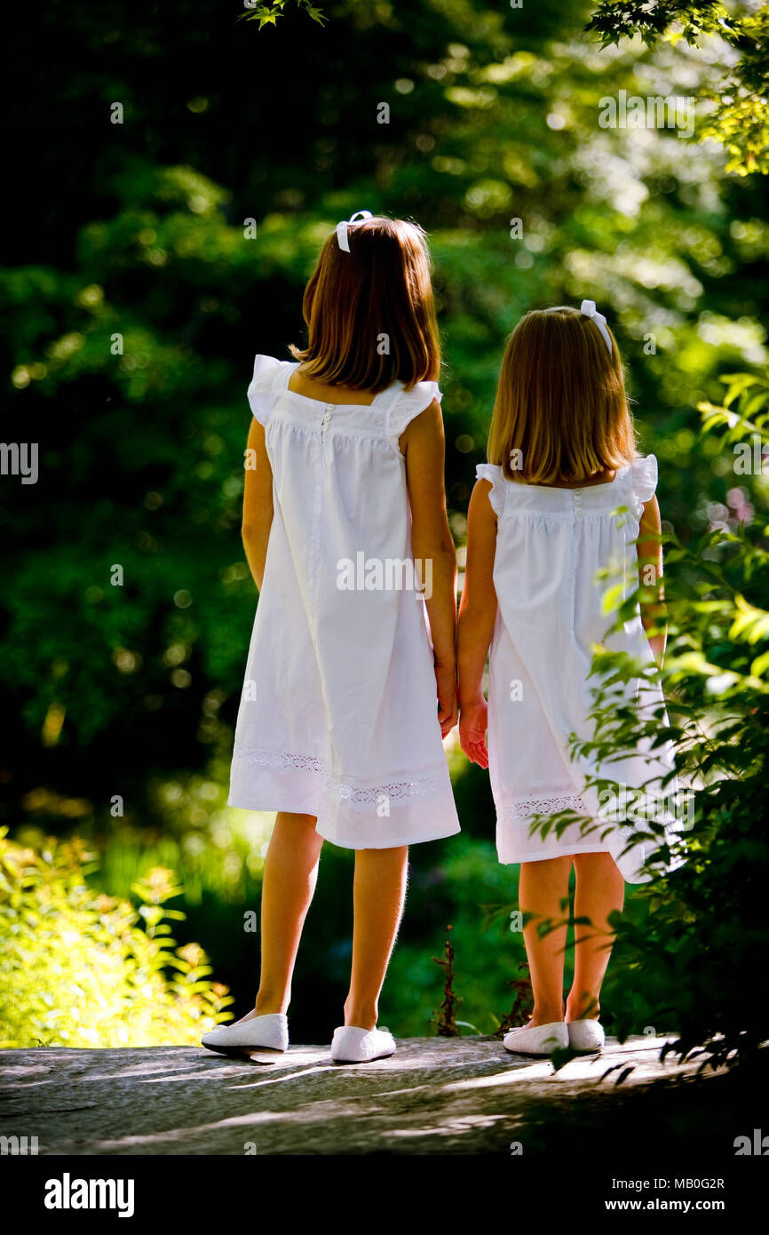 Two young Caucansian girls in matching white skirts and white shoes holding hands looking away from camera posing at a sunny park - Stock Image