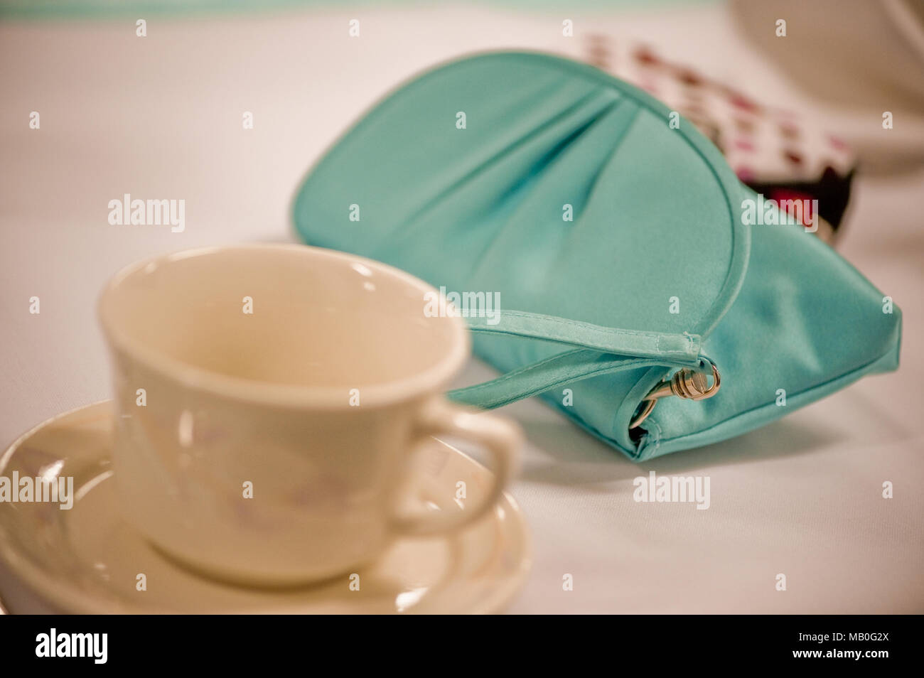 A small teal colored purse next to an empty coffee cup on a table - Stock Image