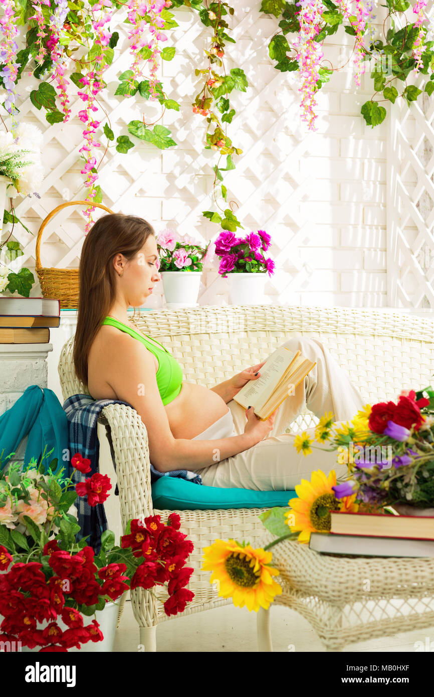 Young pregnant woman reading a book in a summer terrace - Stock Image