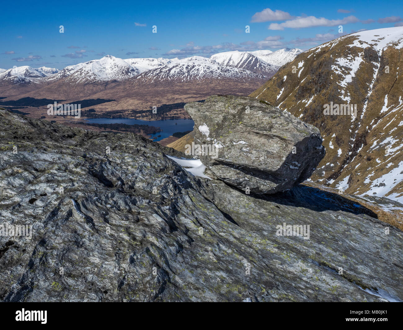 A large rock sitting on the ridge leading to the summit of Beinn Dorain in the Scottish Highlands with the snow capped Blackmount hills in the backgro - Stock Image