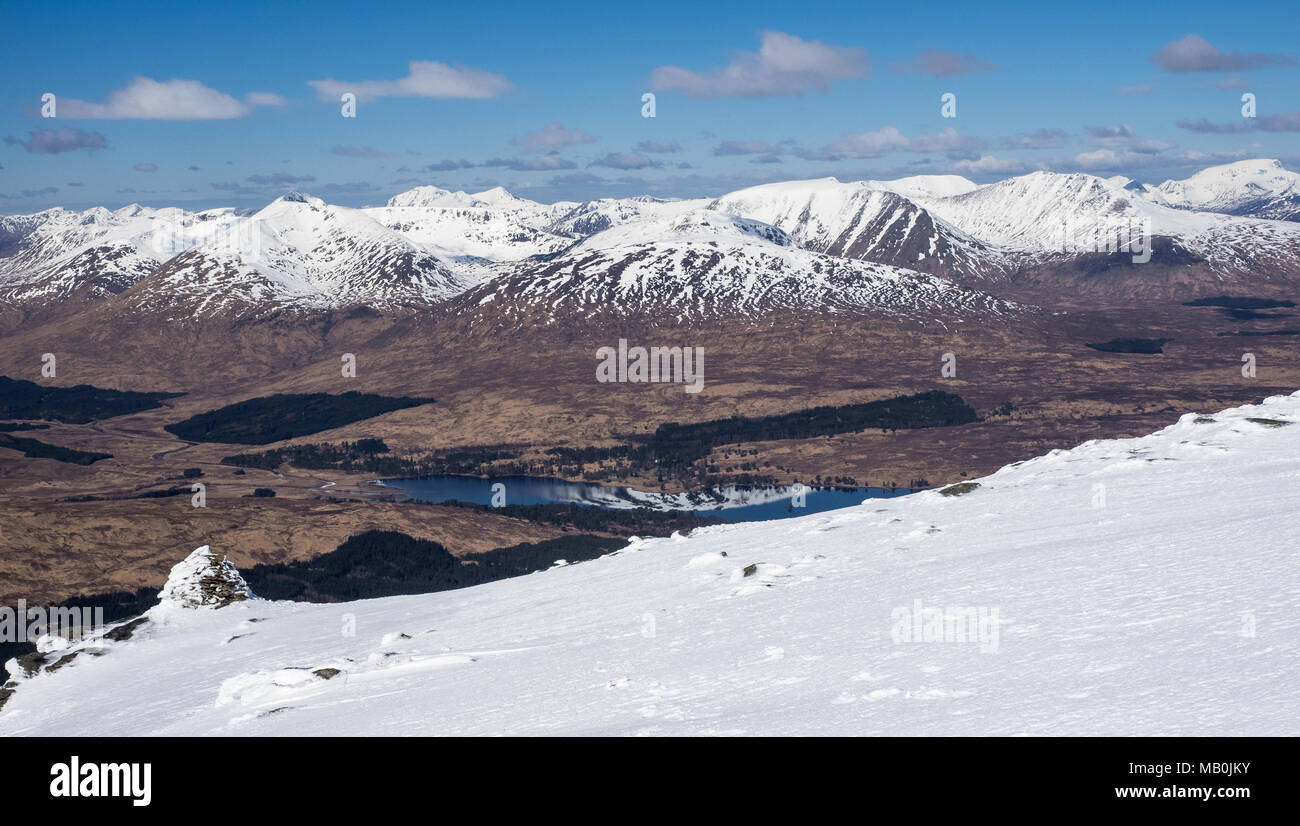 Looking down to Loch Tulla from the summit of Beinn Dorain in the Scottish Highlands with the snow capped Blackmount and Ben Nevis in the background - Stock Image
