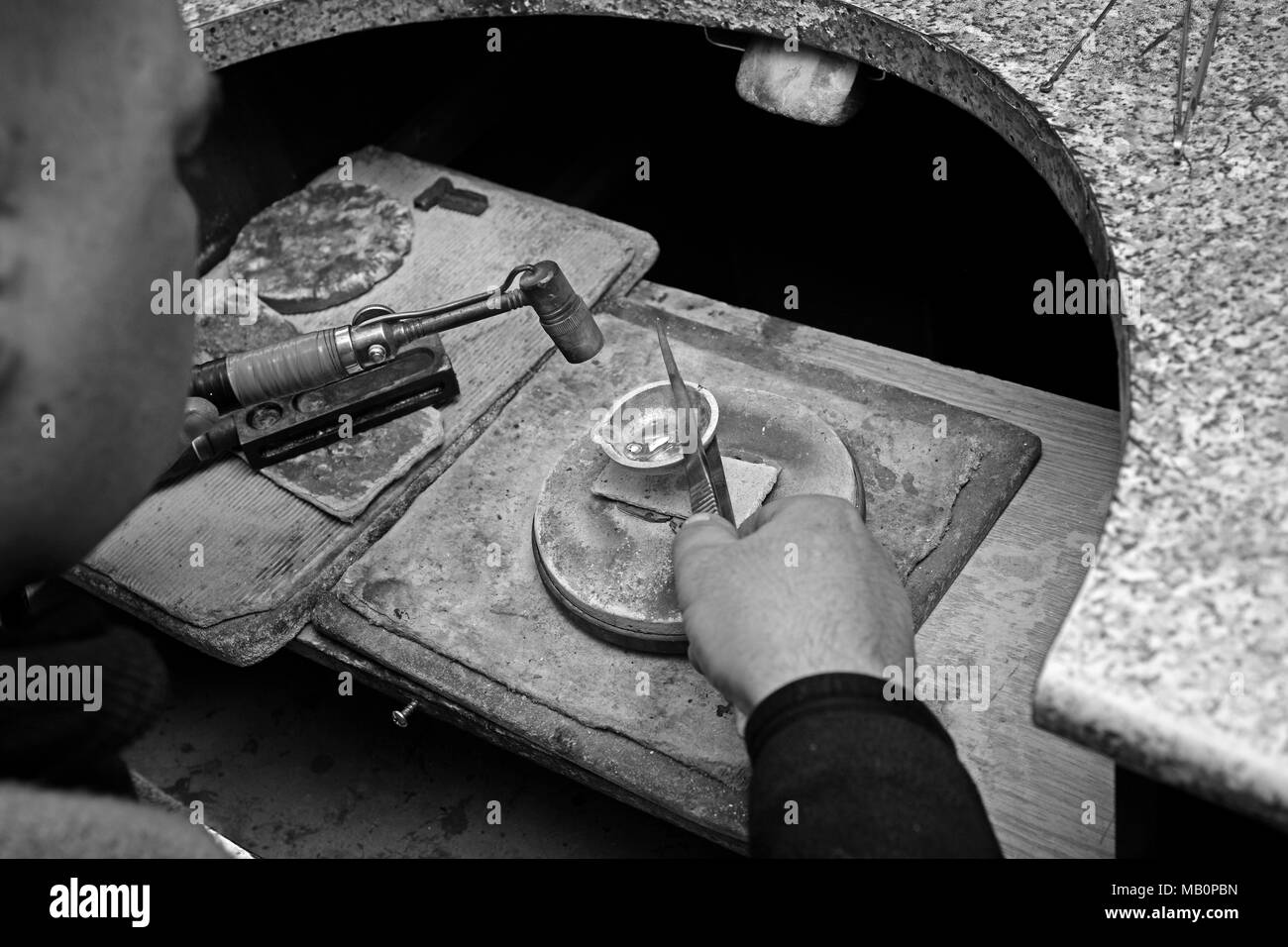 Black and white photo of a jeweler in the workplace. The jeweler melted the gold in the bowl. - Stock Image