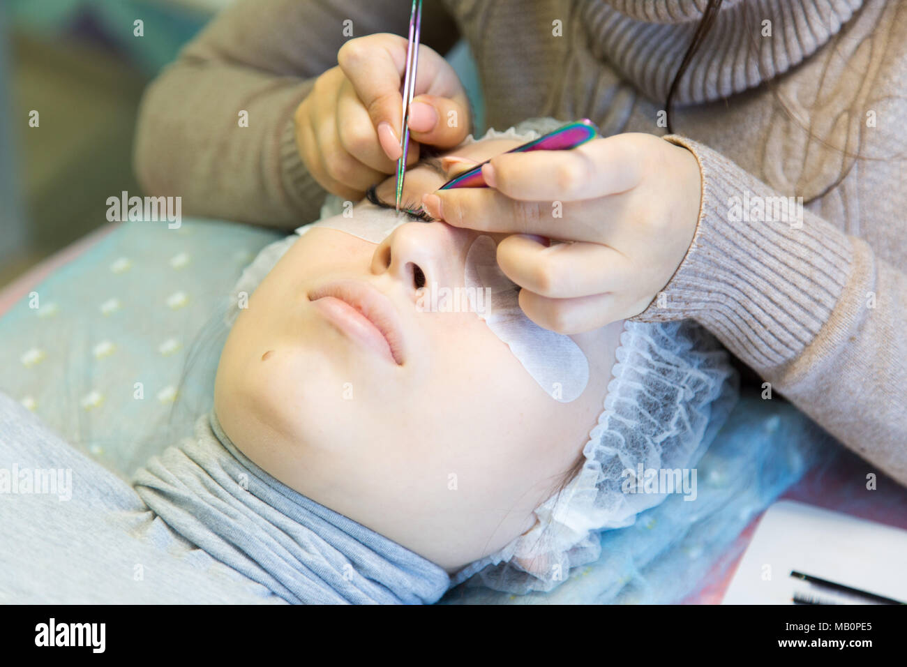 e499940e1c5 The procedure for increasing eyelashes in front of a blonde girl is done by  a master in a beauty salon
