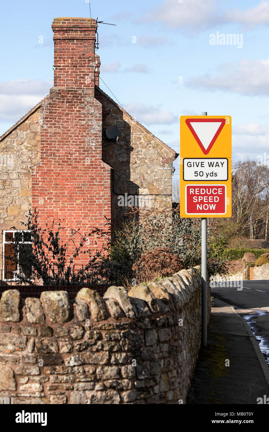 Gable-end of country cottage with an soft focused street sign. - Stock Image