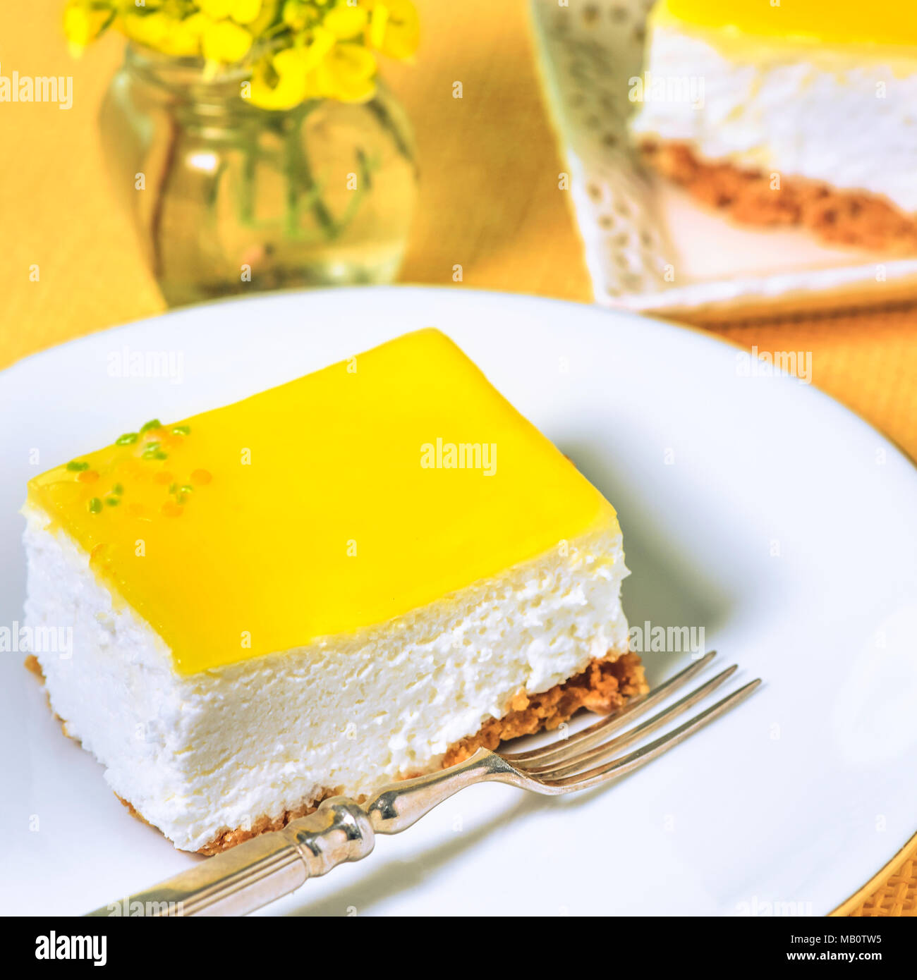 slice of lemon cheesecake on a white place with a silver fork and yellow flowers bokeh background to ad copy space - Stock Image