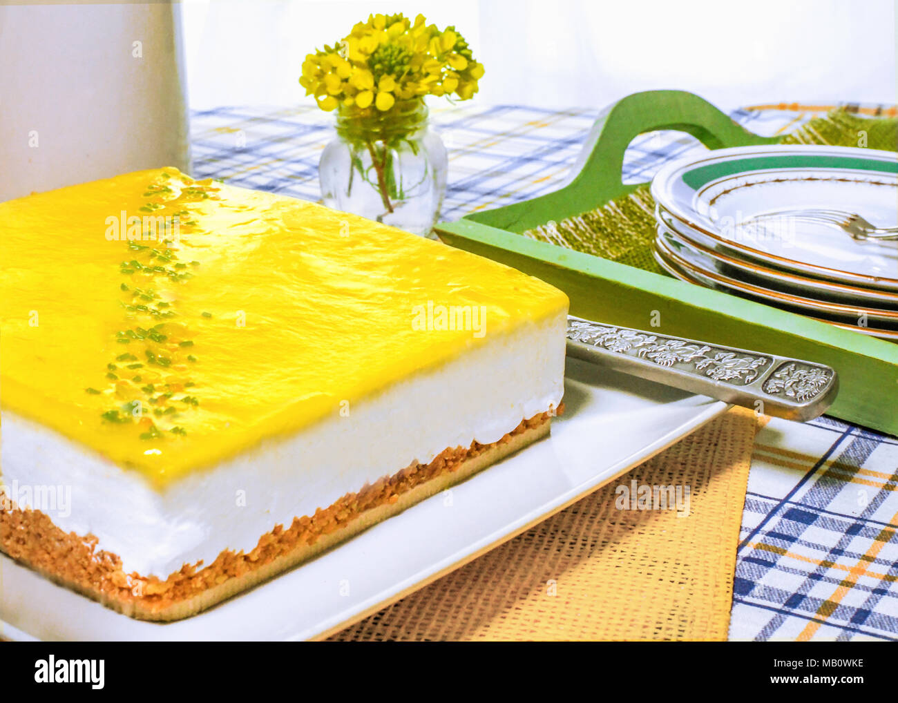 Whole fresh lemon mousse cheesecake in a summer kitchen setting on a table with plates and forks  copy space in the background, - Stock Image