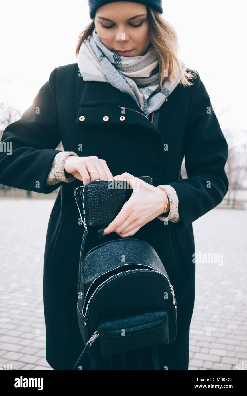 Thrifty young woman happy to save money. Stylish smiling female in black coat, blue scarf and hat opens wallet on the go while walking at street. Sunl - Stock Image