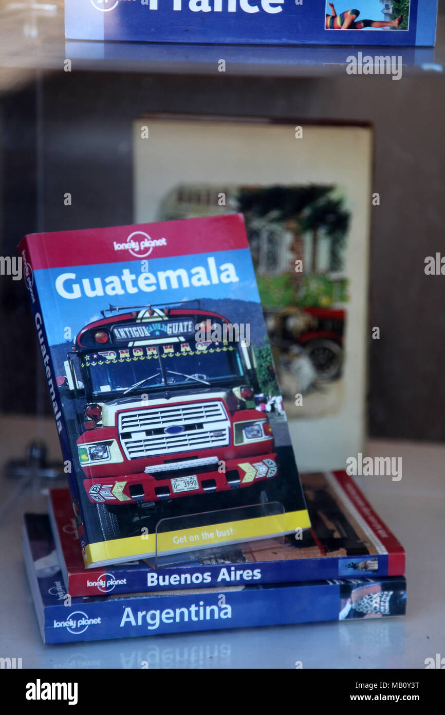 Old travel guides in the window of a second hand bookshop - Stock Image
