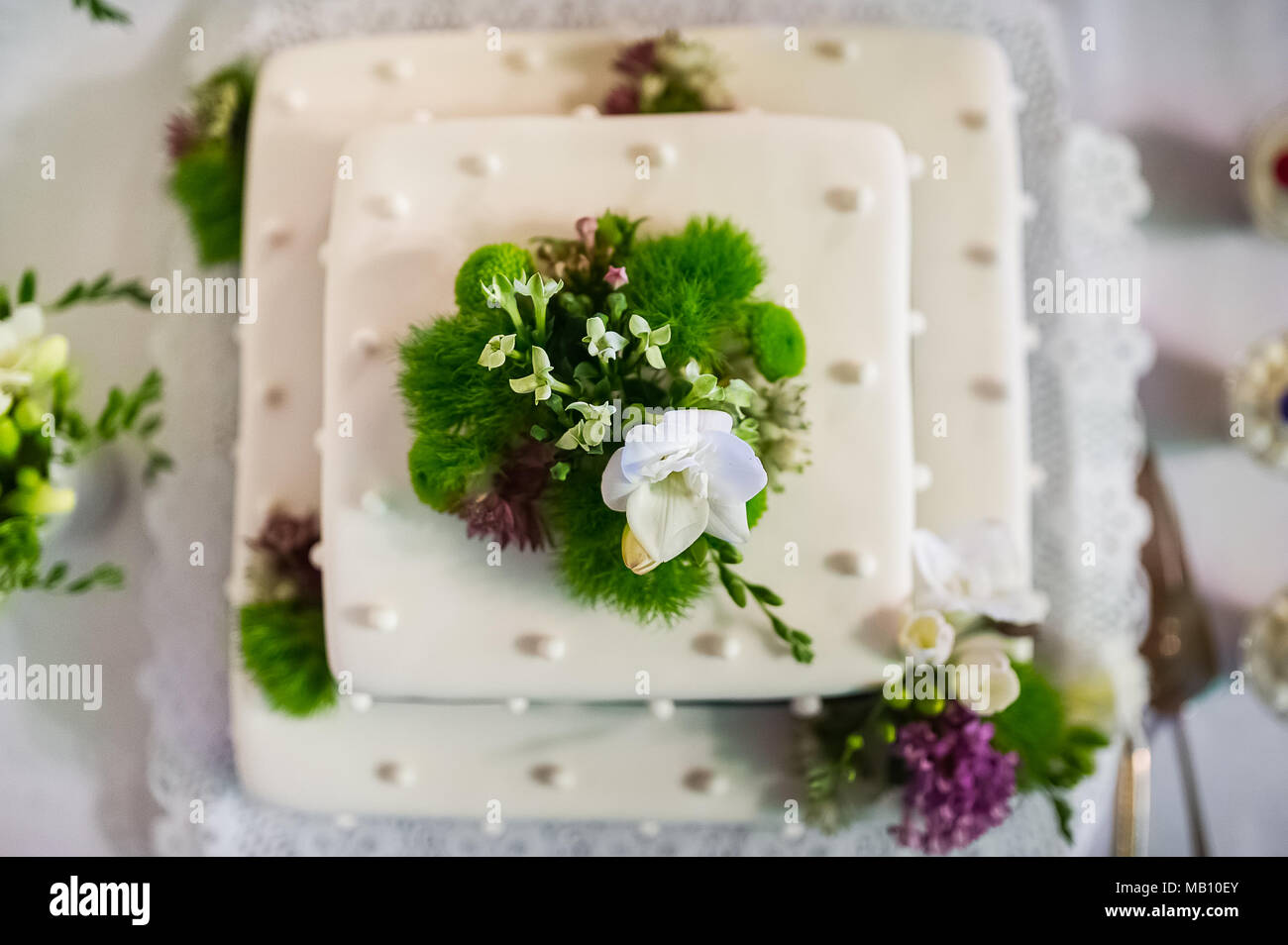Wedding cake with flower decor and white icing - Stock Image
