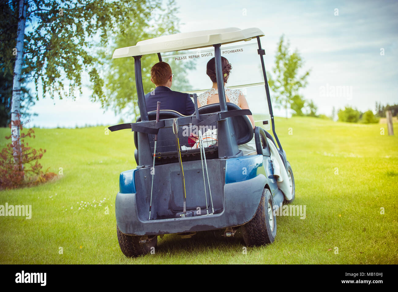 Wedding couple in a golf cart - Stock Image