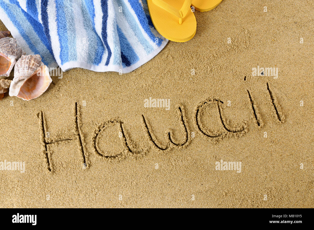 5d205995a7826 The word Hawaii written in sand with flip flops and beach towel - Stock  Image
