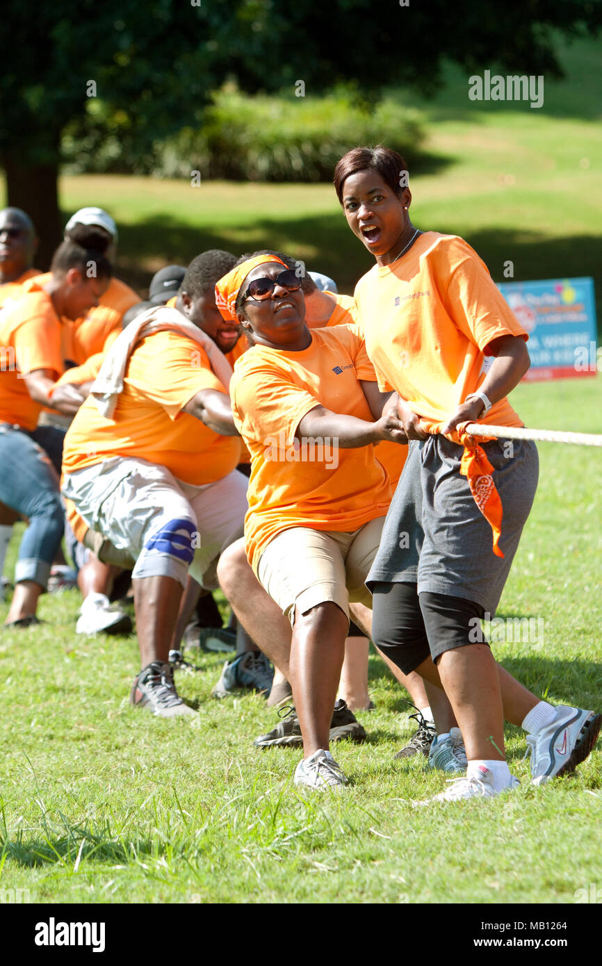 A team pulls in the tug-of-war contest at A Day For Kids, an event where adults play kids games for charity, on September 7, 2013 in Atlanta, GA. - Stock Image