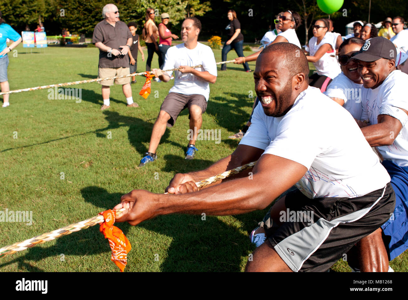 Teams pull hard in the tug-of-war competition at A Day For Kids, an event where adults play kids games for charity on September 7, 2013 in Atlanta, GA. - Stock Image
