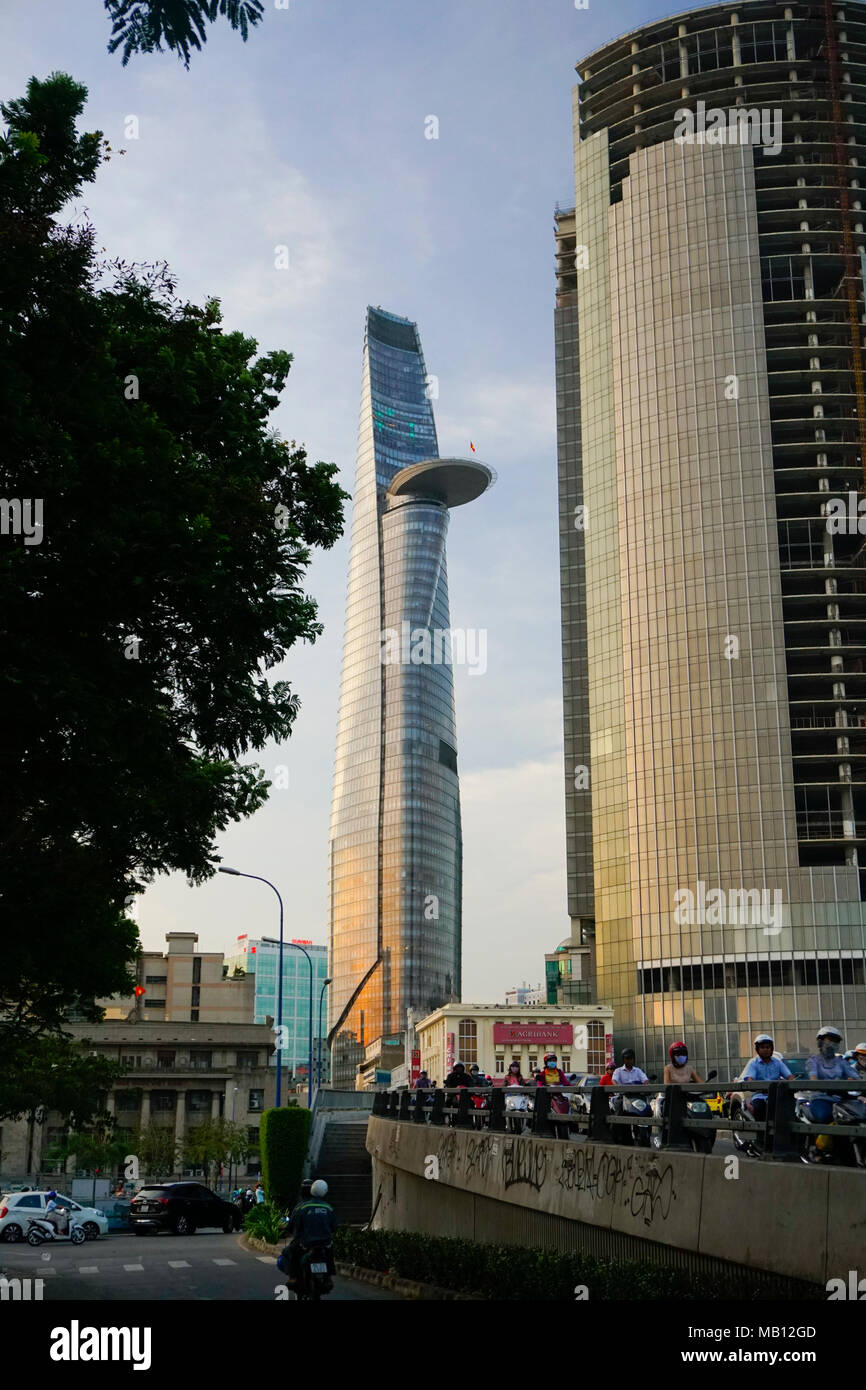 Cau Khanh Hoi Bridge and motorcyclists. District One area, Ho Chi Minh City, Vietnam. The Bitexco Financial Tower. Designed by Carlos Zapata. - Stock Image